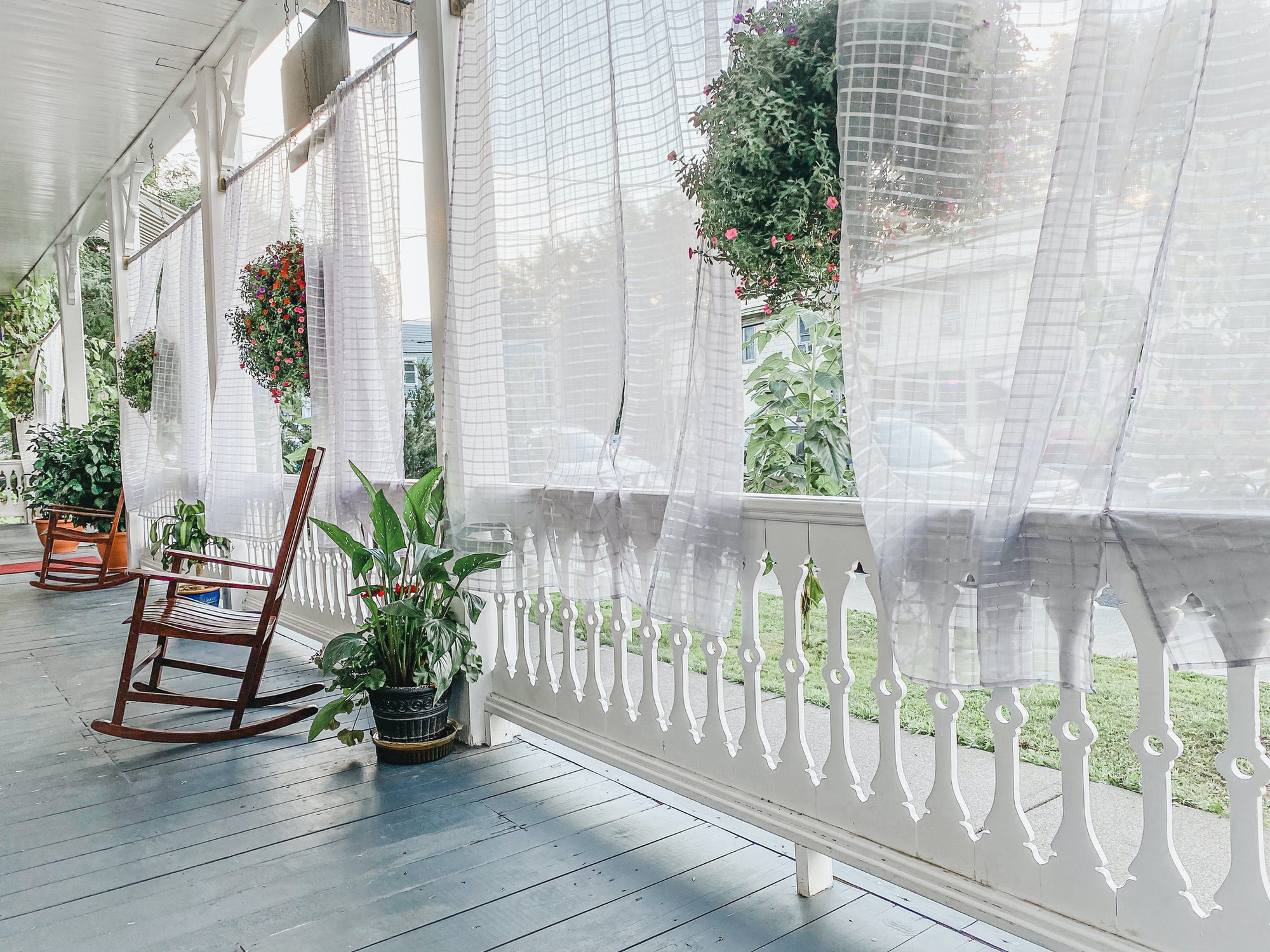 A beautiful summer breeze parts the curtains on an bright and expansive porch.