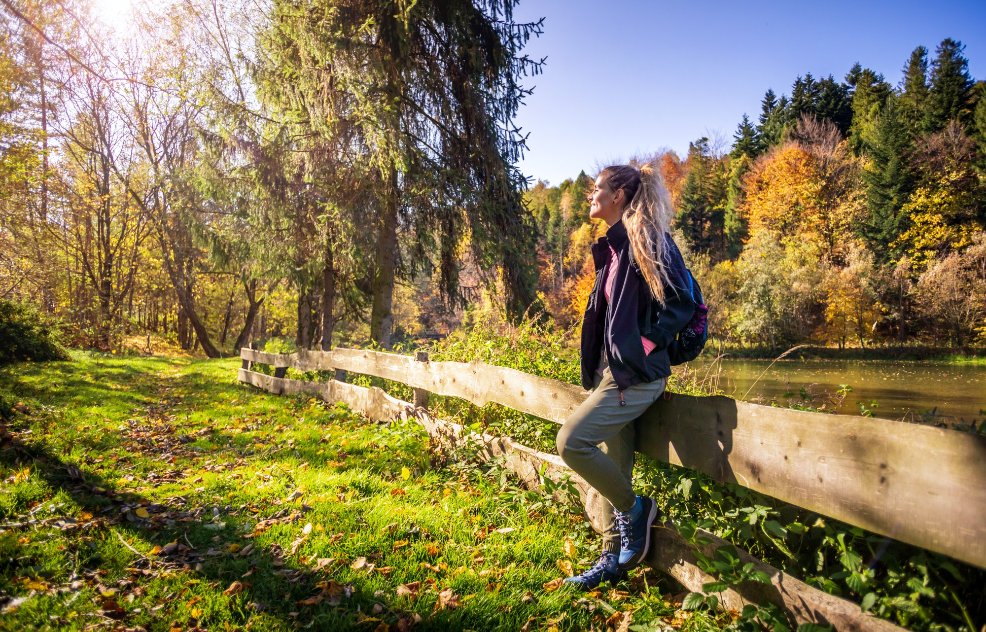 Fall autumn hiker girl at mountains with backpack for camping travel trip